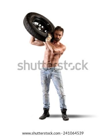 Seductive car mechanic working on a tire - stock photo