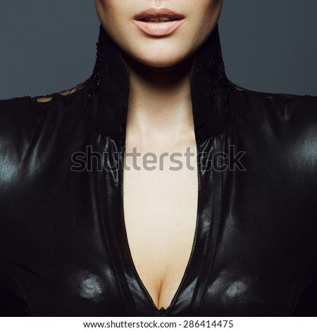 Seductive decollete concept. Portrait of beautiful young woman. Perfect natural make-up. Black leather dress with collar. Healthy skin. Close up. Studio shot - stock photo