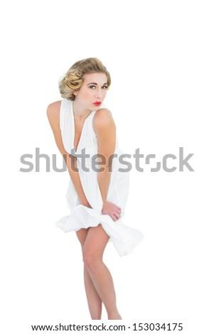 Seductive fashion blonde model posing holding her dress on white background - stock photo