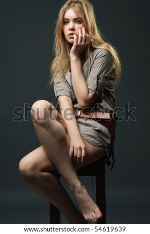Seductive fashion portrait of young woman sitting on chair