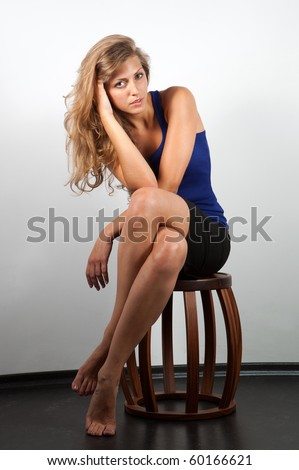 Seductive fashion portrait of young woman sitting on stool - stock photo
