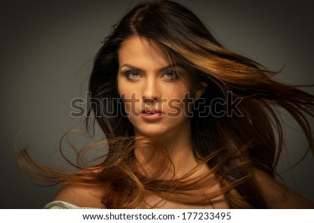 Seductive fatal brunette woman with long hair
