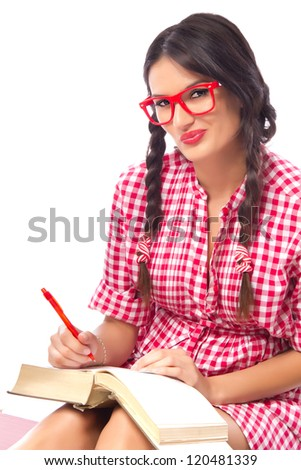 Seductive female student in a nerdy red dress and geek glasses studying, shot on white background - stock photo