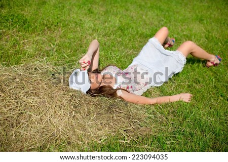seductive girl in cap resting on the grass, legs bent at the knees - stock photo
