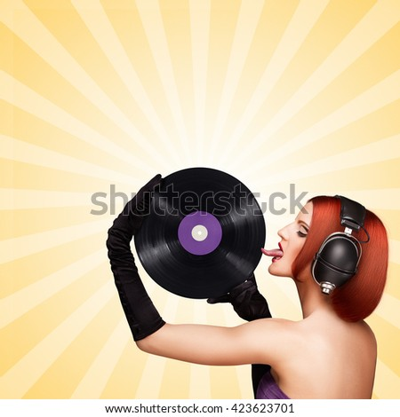 Seductive girl with retro music headphones licking a purple LP vinyl record. - stock photo