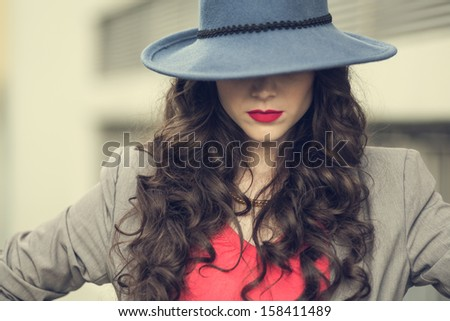 Seductive glamorous brunette wearing stylish clothes posing outside on a cloudy day - stock photo