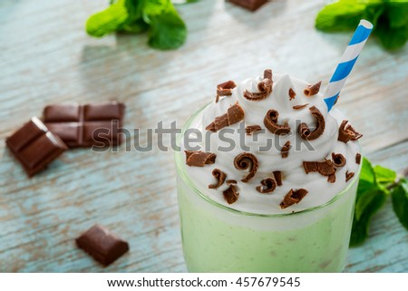 Seductive mint milkshake for sweet tooth consists of ice cream with milk. Pieces of chocolate and leaves of mint for decoration and mixture. - stock photo