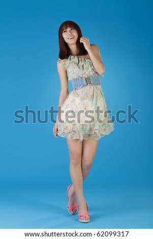 Seductive pretty of Asia on dress posing and smiling over blue background. - stock photo