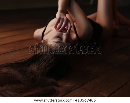 Seductive, sensual and passionate young charming lady in underwear with dark beautiful long hair, closed eyes and sexy figure is lying stretched on the wooden floor and teasing us, finger near lips - stock photo