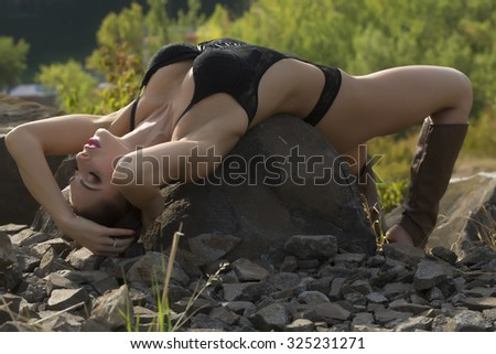 Seductive shapely young woman with black hair and bright makeup in frankly black body and open boots lying with closed eyes on large stone on green trees background in daytime, horizontal photo - stock photo