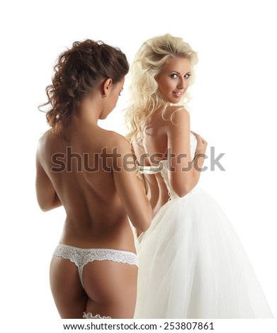 Seductive topless girl helps bride to wear dress - stock photo
