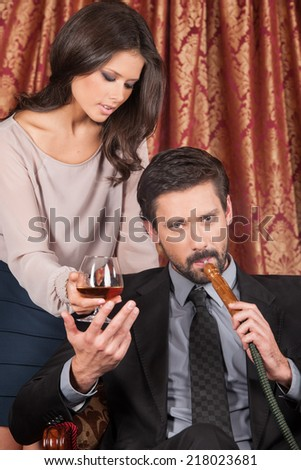 seductive woman standing behind man in Arabic cafe. man inhaling hookah and taking glass of whisky