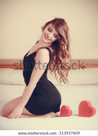 Seductive woman wearing lingerie in bed at home. Attractive sensual young girl with heart shape boxes. Female underwear fashion. Valentines day love. - stock photo
