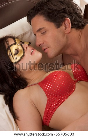 Seductive woman with man, wearing mystery fetish mask - stock photo