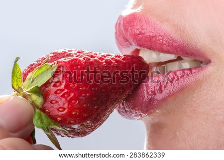 Seductive woman with red lips eating a fresh strawberry - stock photo