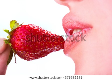 Seductive woman with red lips eating a fresh strawberry