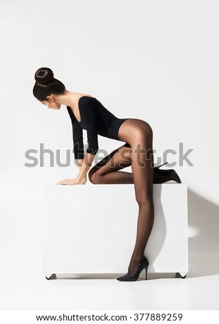 Seductive woman with sexy hips posing in alluring pantyhose over isolated background. - stock photo