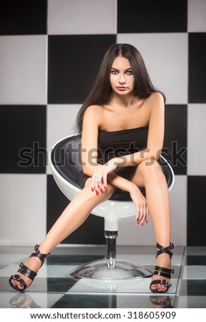 Seductive young brunette posing on a chair in the studio