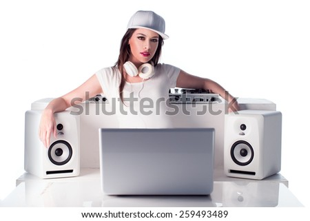 Seductive Young Female DJ with White Headphones and Cap Posing with Music Player, Speakers and Laptop, Isolated on White Background. - stock photo