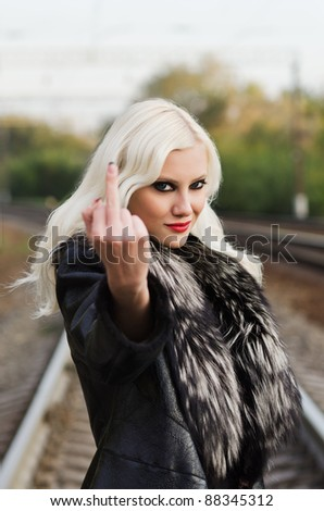 Seductive young girl showing offensive gesture (a middle finger) - stock photo