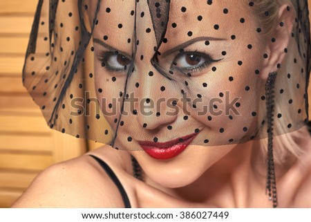 Seductive young woman closeup portrait, veil on face, red lips. Fashion style studio photography. Evening celebration makeup. - stock photo