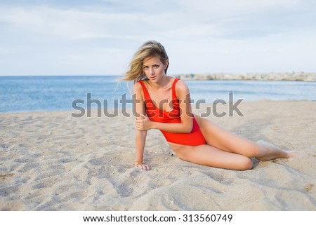 Seductive young woman dressed in sexy swimsuit sitting on the beach against sky and sea background with copy space area for your text message or content, charming female in red bikini posing outdoors - stock photo