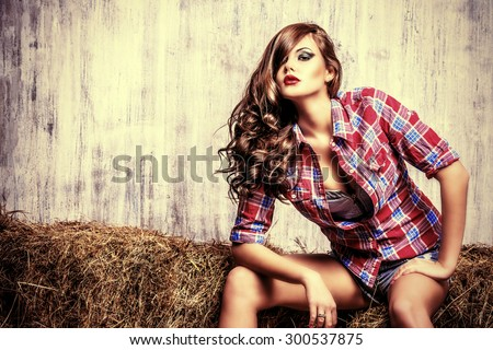 Seductive young woman in jeans shorts and a plaid shirt alluring on a hay.  fashion. Western style. Beauty, fashion. - stock photo
