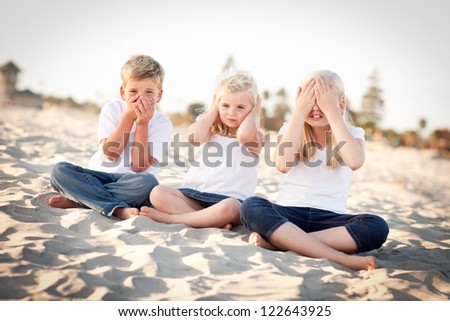 See, Hear and Speak No Evil Posing Children Outside at the Beach. - stock photo