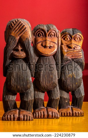 See hear speak no evil carved wooden monkeys on red background full body facing front - stock photo
