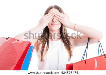 See no evil concept with smiling shopaholic woman covering her eyes and holding colored bags isolated on white studio background - stock photo
