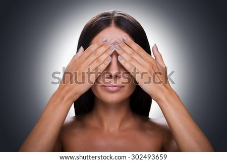 See nothing! Portrait of young shirtless woman covering eyes by hands while standing against grey background