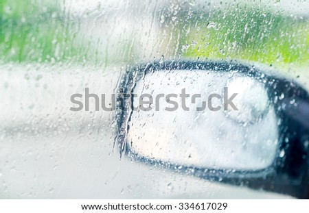 See through car window to side rear-view mirror in raining day - stock photo