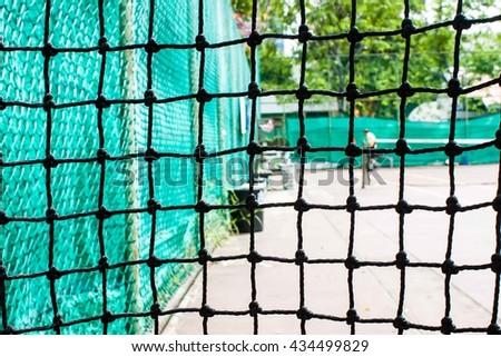 see views tennis court though nylon nets - stock photo