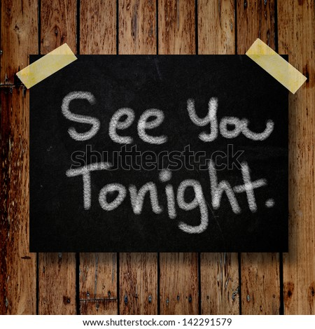 See you tonight note on message note with wooden background - stock photo