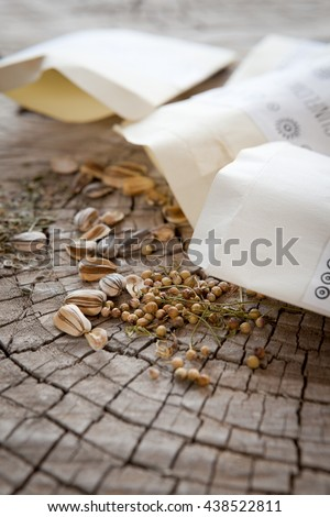 Seed packets and seeds. Focus on coriander and sunflower seeds, dill seeds farther back. - stock photo