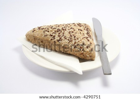 seeded bread roll on a plate with paper napkin and knife - stock photo