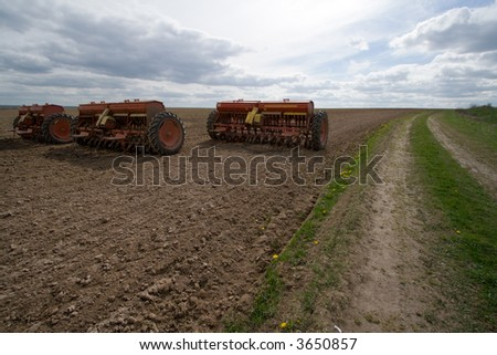 Seeding machines at field and road. - stock photo