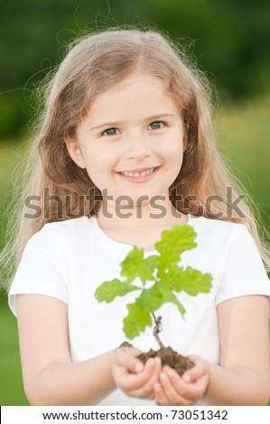 Seedling - little girl and young plant of a oak - stock photo