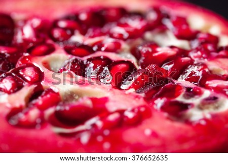 Seeds of fresh pomegranate with water droplets on a dark background, closeup, selective focus