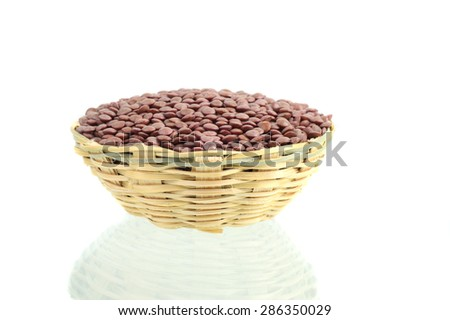 Seeds of Red Lentils in wooden basket on white background - stock photo