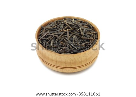Seeds of wild rice in a wooden dish on a white background