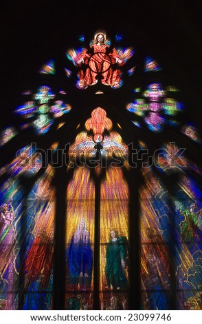 Seeing the light and peace concept with light shafts coming through stunning stain glass Church Window as Christ holds out his hands with a Dove underneath - stock photo