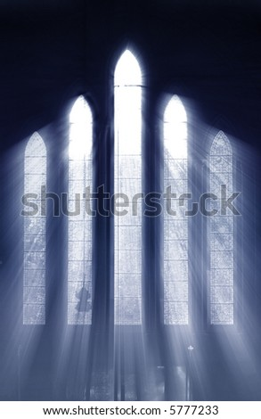 Seeing the light, shafts of light stream through stained glass window and onto cross below - stock photo