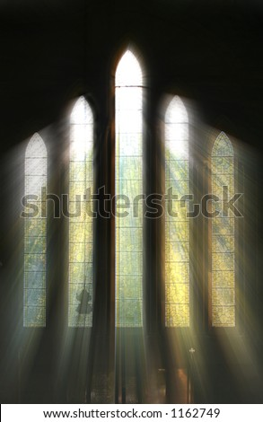 Seeing the light, shafts of sunshine stream through stained glass window and onto cross below - stock photo