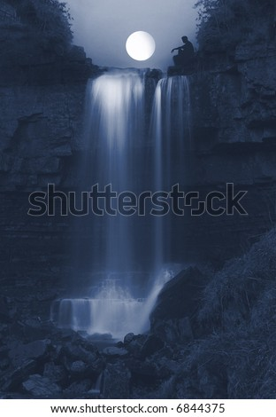 Seeing the light, young Man  sitting  on rocks on the top of the powerful Ashgill Waterfall in England lit by the Moon - stock photo
