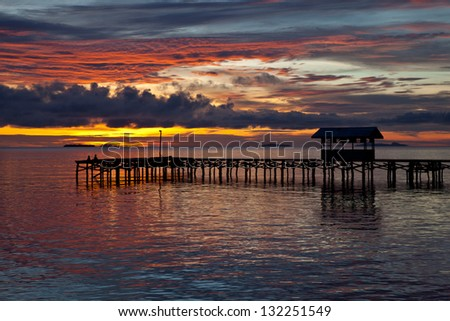 Seen from a Papuan village, the last sunlight of the day lights the clouds above the Dampier Strait in Raja Ampat, Indonesia.  This body of water is full of marine life and offers excellent diving. - stock photo