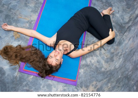 Seen from above, a brown haired caucasian woman doing yoga exercise, Ardha Jathara Parivarttanasana Pose or Half Revolved Belly posture  on yoga mat in studio with mottled background. - stock photo