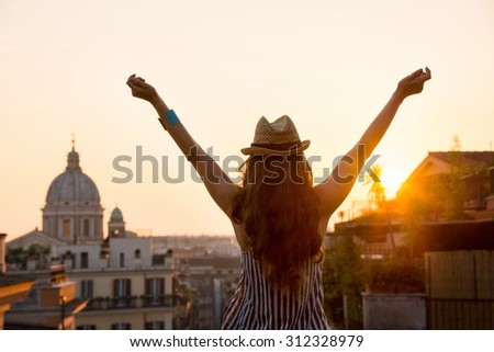 Seen from behind, a woman is standing with outstretched arms, looking out at the city of Rome at sunset in summer.