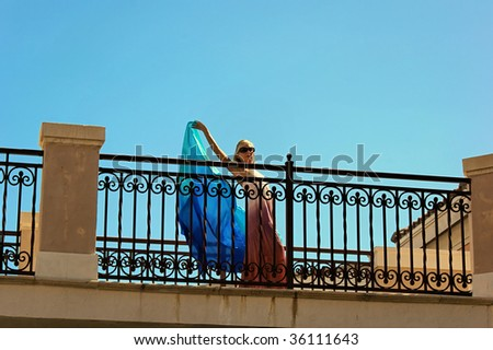 seen from below, an attractive blonde woman wearing a long dress and holding a blue veil is dancing across an outside balcony. with room for text - stock photo