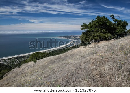 Seen from hiking trails in the hills, the gentle curve of Stinson Beach, just north of San Francisco, California, stretches northward on a sunny day. - stock photo